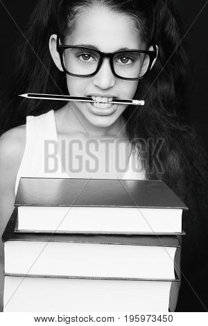 Little Girl With Glasses And Pencil Holds Books And Looks At Camera