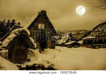 Snow Covered The Ground In Winter. Town With Night Sky And Full Moon. Sepia Tone.