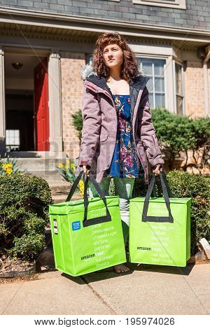 Fairfax USA - March 2 2017: Amazon Fresh insulated grocery delivery bags on front porch closeup with woman standing holding them