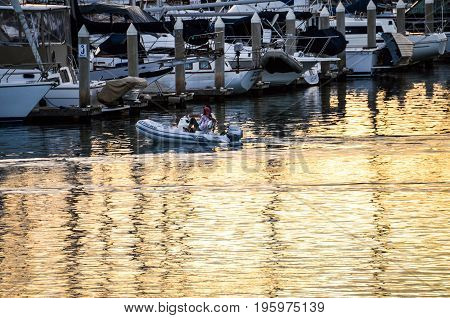 Oxnard, Usa - March 9, 2014: Couple Riding Boat In Harbor During Sunrise In California