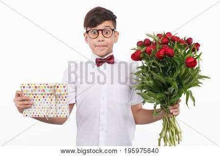 Little boy in glasses and bow tie holding bouquet and giftbox looking surprisingly at camera.
