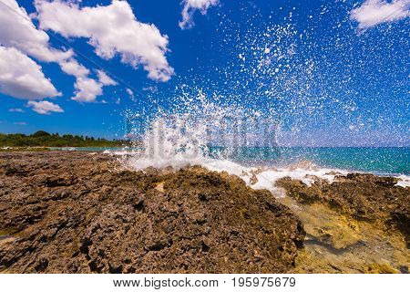 Water splashing - crystal clear sea water beating against the rocks. In Bayahibe La Altagracia Dominican Republic. Copy space for text