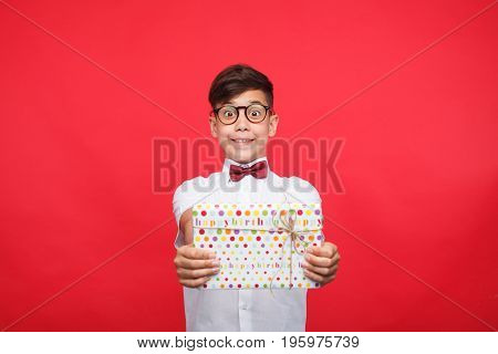 Kid in glasses outstretching hands with giftbox looking happy on red background.