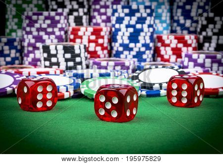 Stack of Poker chips and dice on a green gaming poker table. Poker dice at the casino . Playing a game with dice. Casino dice. Concept for business risk chance good luck or gambling. chips and dice for poker