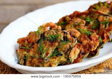 Fried eggplant cutlets. Crispy eggplant cutlets with garlic and dill on a white plate and a vintage wooden table. Easy vegetarian eggplant recipe. Closeup