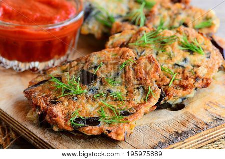 Quick and easy eggplant cutlets. Fried eggplant cutlets with garlic and dill on a wooden board. Tomato sauce in a glass bowl. Healthy veggie recipe. Closeup