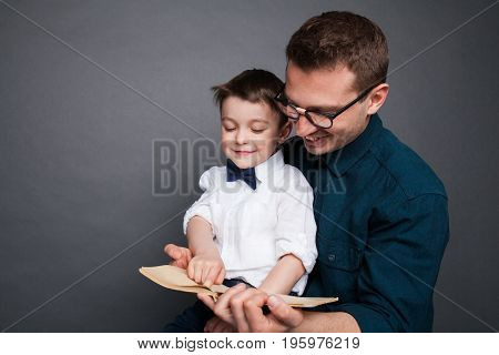 Man in glasses holding kid on knees and reading book on gray background.