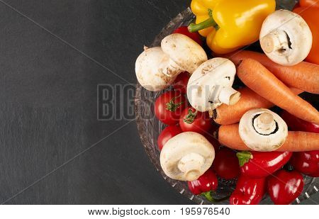 Close up healthy fresh salad ingredients with carrot mushroom tomato and bell pepper on glass bowl placed on dark stone kitchen table. Black textured background with copy space. Healthy food