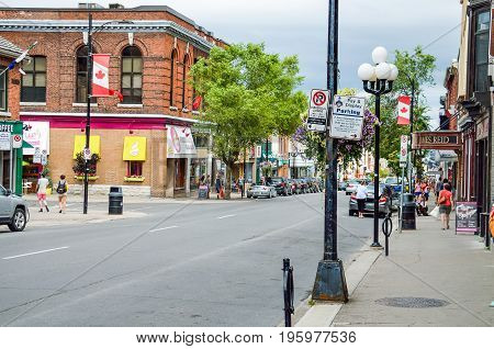 Kingston Canada - July 23 2014: Downtown city in summer with Canadian flags and people walking on main street