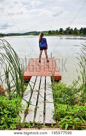 Young woman standing on small dock overlooking lake
