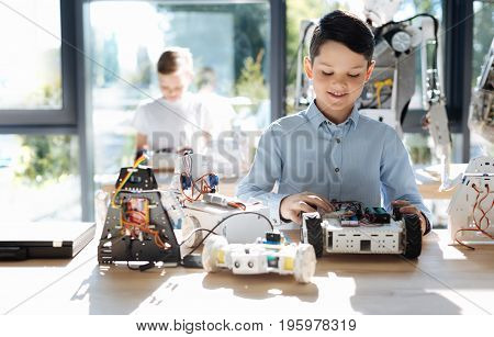 Young investigator. Handsome pre-teen boy sitting at the table full of robots and examining the front part of his robot car while his friend sitting behind him