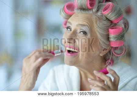 Close up portrait of senior woman in white bathrobe applying pink lipstick