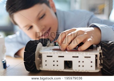 Intricate parts. The focus being on a cute hand of a cheerful little boy adjusting a part with wires in his robotic vehicle