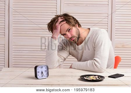 Man Sits At Wooden Table With Alarm Clock And Pills
