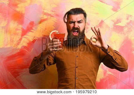 Bearded man long beard. Brutal caucasian happy hipster with moustache in brown shirt holding tropical alcoholic fresh cocktail with orange piece on colorful texture background