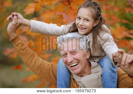 happy grandfather and granddaughter in a park