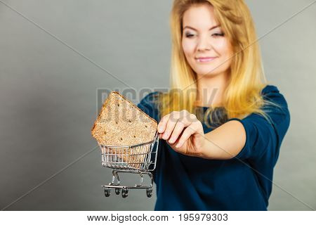 Buying gluten food products concept. Woman holding shopping cart trolley with small piece of bread