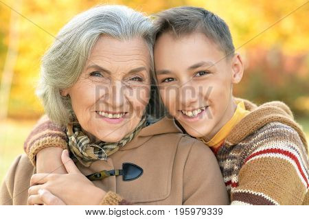 Portrait of a grandmother and grandson hugging in a park