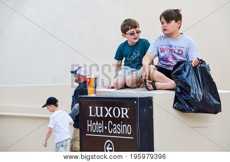 Las Vegas, Usa - May 7, 2014: Closeup Of Children Sitting Outside By Luxor Hotel And Casino Sign