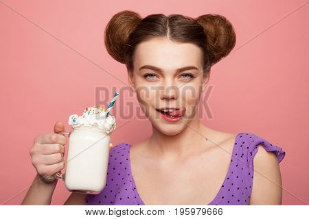 Brunette girl with hair buns holding cup with milkshake licking lips wearing purple shirt with black dots.