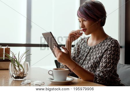 Side view of pretty woman using tablet sitting in cafe and having a cup of coffee.