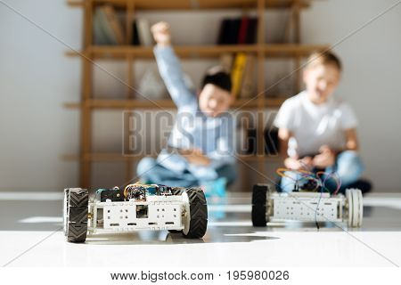 Pleasant victory. The focus being on two robotic vehicles standing on the floor while to boys controlling them in the background and one of them raising a hand in gesture of triumph, having won