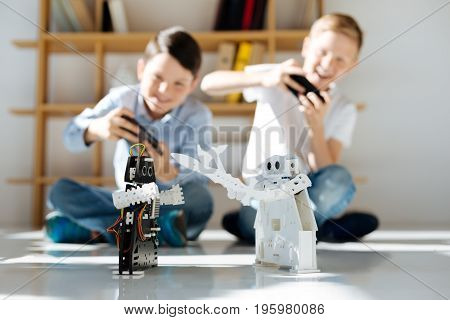 Quality time. Two happy pre-teen boys sitting on the floor and controlling two cosmic warrior robots fighting with each other