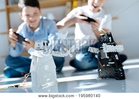 Having fun. Two excited pre-teen boys sitting on the floor and controlling the fight between black and white robotic warriors, seemingly enjoying themselves