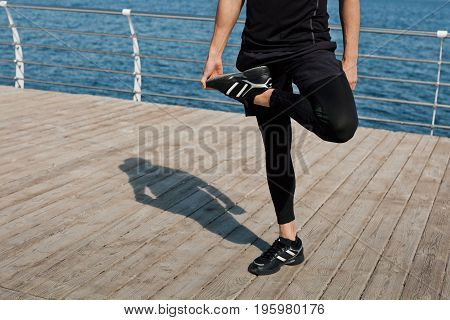 Faceless shot of man in sportswear stretching leg while standing on pier with sea on background.