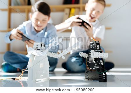 Excited players. Upbeat little boys sitting on the floor, holding game controllers and playing with their new black and white robots, fighting each other with them