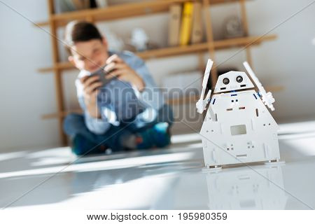 Favorite toy. Dark-haired little boy sitting on the floor, holding a game controller and making his white robot move