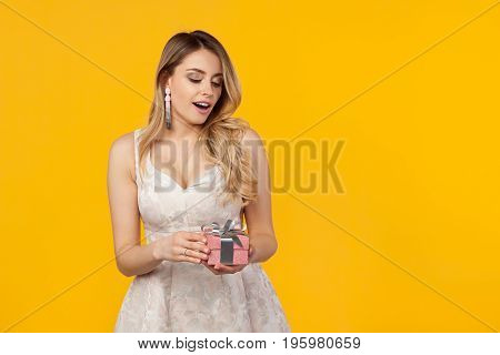 Young beautiful woman in white dress holding small giftbox and looking excited on orange.