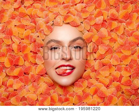 From above shot of woman lying in fruit jelly and biting candy looking at camera.