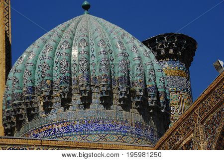 Registan medrese details - bright multicolored dome and minaret against blue sky background. Registan is the heart of the ancient Samarkand city.