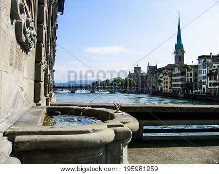 Zurich, Switzerland - August 11, 2007: Water Fountain With River, Bridges And Cityscape During Summe
