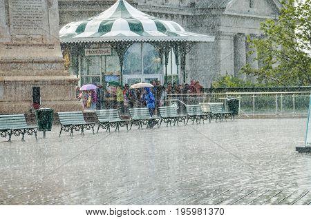 Quebec City Canada - July 27 2014: Crowd of people walking in heavy rain on Dufferin terrace boardwalk street close to Chateau Frontenac