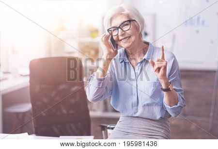 Wait a minute, please. Graceful hardworking inspiring lady conducting negotiations with the client and suggesting her colleague waiting for a moment until she finished
