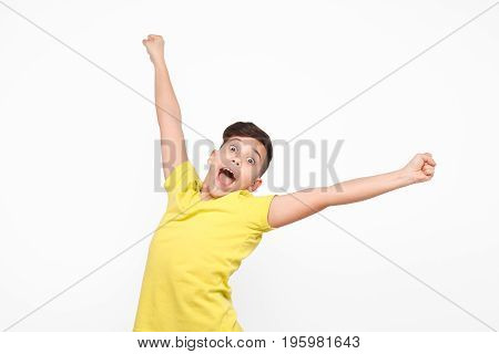 Cheerful boy in yellow t-shirt looking at camera while posing excitedly with hands up on white background.