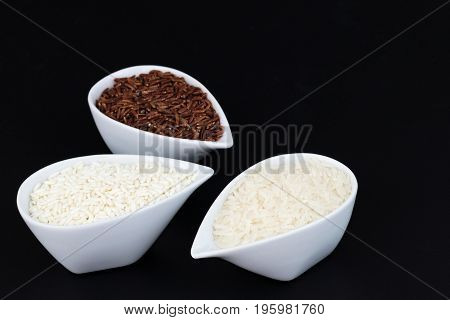 3 kind of raw Thai rice Thai Jasmine rice(Hom Mali ), Glutinous/Sticky Rice (Khao Neow), Brown Rice (Khao Dum) in white cups on black background with copy space