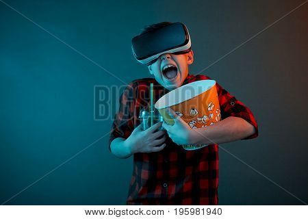 Horizontal studio shot of amazed kid with mouth opened holding popcorn basket and drink wearing VR headset.