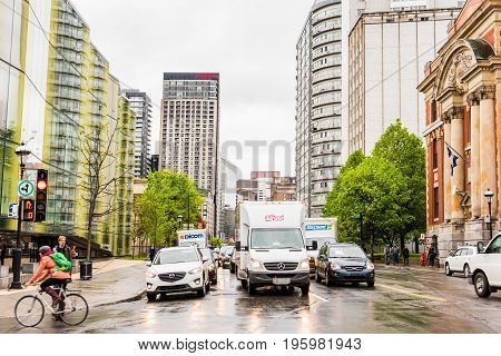 Montreal Canada - May 26 2017: People walking in Montreal's downtown area in Quebec region with Hilton Garden Inn hotel and wet roads