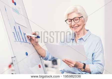 Ambitious specialist. Charismatic positive mature lady standing by whiteboard and reading a data while creating another picture with a marker