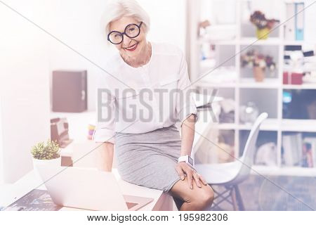 Making appointments. Brilliant bright mature woman sitting on the table and looking delighted while typing something on her laptop