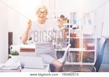 New day and new opportunities. Passionate senior business lady expressing her feelings after completing a task while sitting on the table