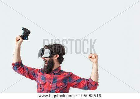 Young bearded man wearing VR headset and holding hands up in gesture of victory.
