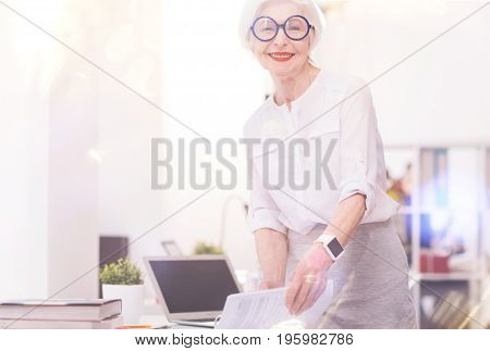Just a sec to take something. Clever elegant energetic lady stopping by her table and grabbing the documents before leaving for the meeting with clients