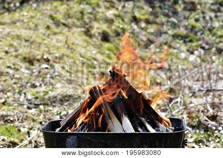 Wood fire. Photo of fire brown wood dark grey black coals on bright yellow fire inside metal brazier.Wood burning in the braziers.Flames fires preparation for cooking barbecue.Brazier of nature bbq background.