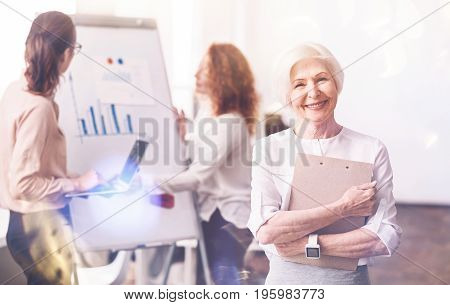 Preparing for lecture. Inspiring dedicated senior lady holding a folder with her notes while her colleagues fixing the illustrative material before starting a meeting