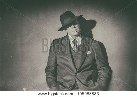 Antique Black And White Photo Of 1940 Film Noir Gangster Wearing Suit And Hat. Smoking Cigarette. St