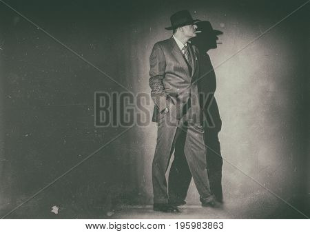 Antique Black And White Photo Of Film Noir Man Wearing Suit And Hat. Smoking Cigarette.